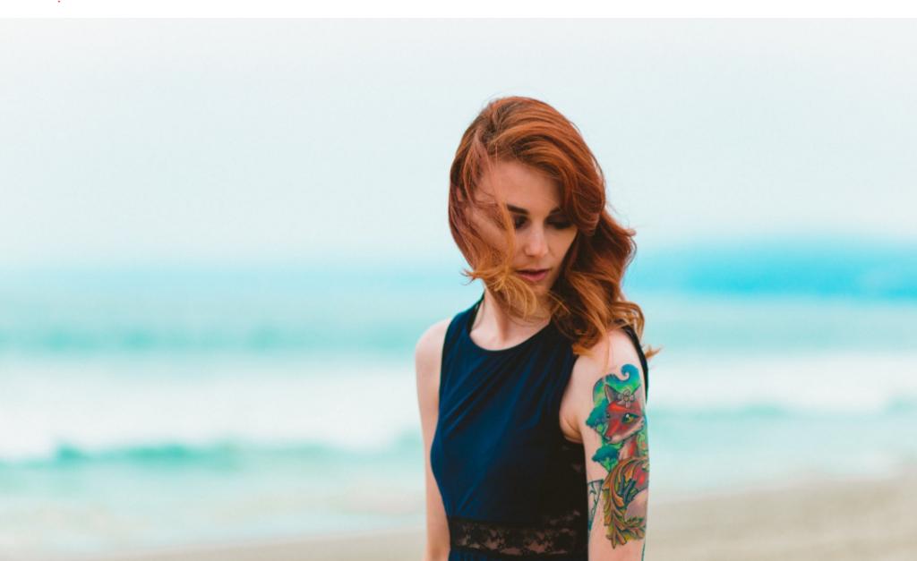 Tattoo Esbjerg kvinde der står foran havet med sin nye tatovering i Esbjerg